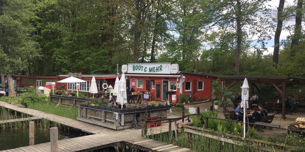 Bild, das die Steganlage von Boot & Mehr am Kleinen Pälitzsee zeigt, ein roter Flachbau mit blumengeschmücktem Biergarten davor.