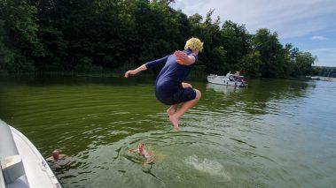 Das Bild zeigt einen Teenager beim Sprung mit angewinketen Beinen vom Boot in einen See.